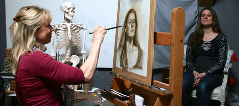 Lindy painting an oil portrait in her studio with the sitter